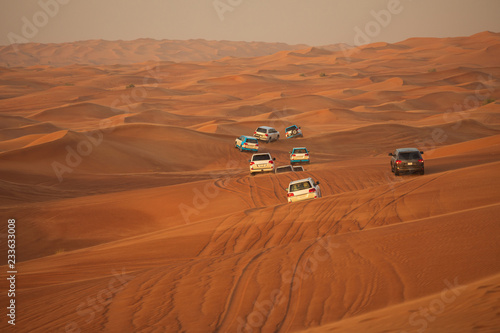 fototapeta na ścianę Off-road adventure with SUV driving in Arabian Desert at sunset. Offroad vehicle bashing through sand dunes in Dubai desert. Traditional entertainment for tourists