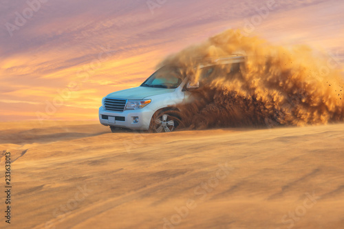 Off-road adventure with SUV in Arabian Desert at sunset. Offroad vehicle bashing through sand dunes in Dubai desert.