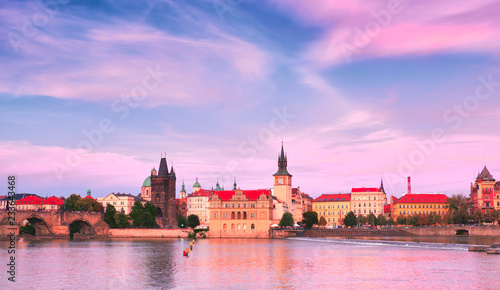 Prague, riverside on sunset, with Charles Bridge on the right and historic skyline in front