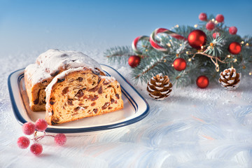 Christmas stollen on white-blue festive background with fir twigs and trinkets, copy-space