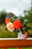 Fresh tender pink and red garden roses stand on wooden porch in glass on the background of a country house in soft-focus in the background - 233679649