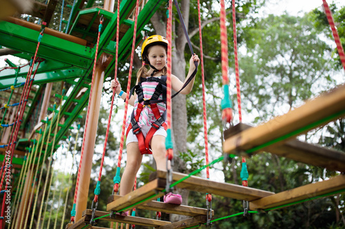 Leinwandbild Motiv Child in adventure park. Kids climbing rope trail.
