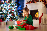 Kids at Christmas tree. Children open presents © famveldman