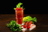 Glass of fresh tomato juice decorated with celery and pepper and a branch of red tomatoes on a wooden table isolated at black background.