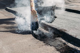 Worker repairs the roof with molten tar from a bucket with a broom. - 233722820