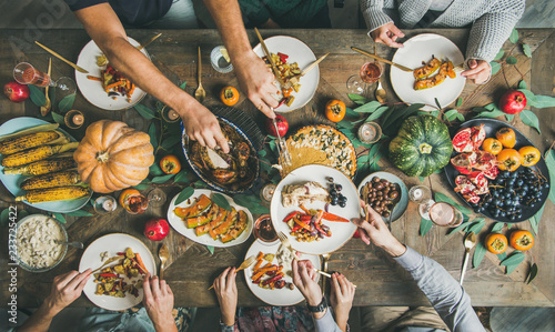 Traditional Thanksgiving or Friendsgiving holiday celebration party. Flat-lay of friends feasting at Thanksgiving Day table with turkey, pumpkin pie, roasted seasonal vegetables and fruit, top view - 233725422