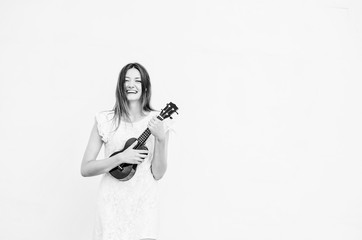 Black and white shot of Young beautiful woman playing ukulele and having fun