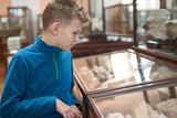 A teenager boy examines exhibits at the Museum of Natural History. A teenager boy exploring exhibits in the geological museum. - 233731050