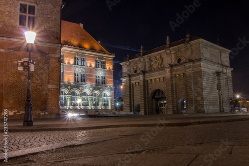 fototapeta na ścianę Old historic Gate in Gdansk at night, Poland, is one of the city's most notable tourist attractions.