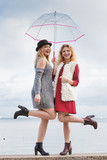 Two fashionable women and umbrella - 233755491