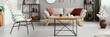 Wood and metal coffee table with candles and tea cup in bright living room interior with grey lounge with cushions and chair, metal racks with decor and plant in vase in real photo - 233762431
