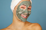 Beautiful cheerful teen girl applying facial clay mask. Beauty treatments, isolated on blue background. © Khorzhevska