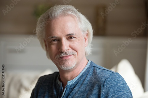 Leinwanddruck Bild Close up portrait of smiling aged man with moustache looking at camera relaxing at home, happy senior male posing shooting indoors, elderly husband making professional photo or picture for album