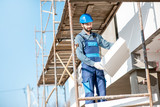 Builder warming a building facade with foam panels standing on the scaffoldings on the construction site - 233791457