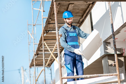 Obraz na płótnie Builder warming a building facade with foam panels standing on the scaffoldings on the construction site