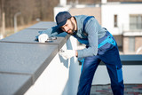 Builder in uniform mounting metal cover on the parapet of a new building - 233792032