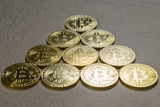 bitcoin coins on a gold background - 233810497