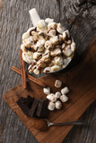 A mug of hot cocoa with toasted marshmallows next to a cutting board with chocolate chunks and cinnamon sticks, vertical - 233820057