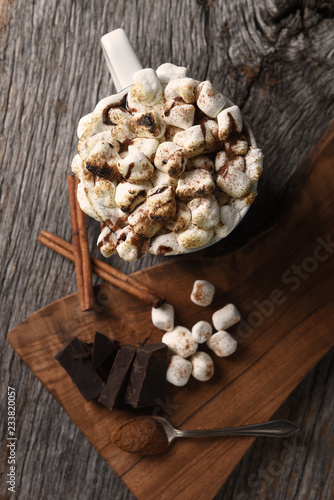 fototapeta na ścianę A mug of hot cocoa with toasted marshmallows next to a cutting board with chocolate chunks and cinnamon sticks, vertical