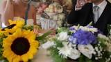 Fiori a centrotavola di un tavolo con due sposi che brindano e bevono due calici di spumante - 233836497