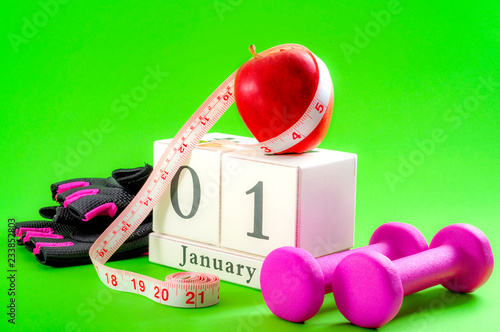 Leinwanddruck Bild New year resolution, start a diet and stop procrastinating concept with an apple, pink dumbbells and gym gloves next to a cube calendar showing the date of january 1st on bright vivid green background