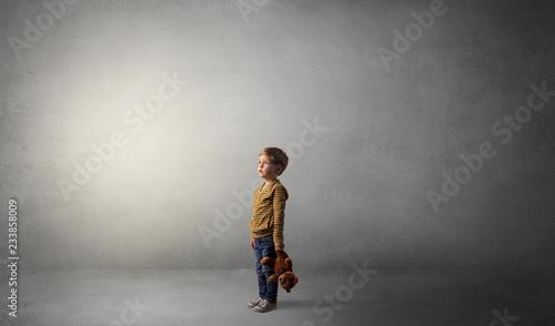 Leinwandbild Motiv Little waggish kid staying alone in a big empty room with his plush