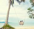 Leinwandbild Motiv Young couple swinging on a swing on paradise tropical beach, honeymoon, vacation, travel concept