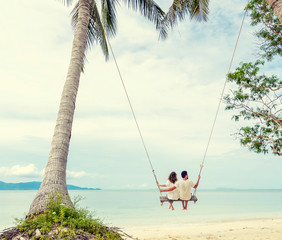 Young couple swinging on a swing on paradise tropical beach, honeymoon, vacation, travel concept