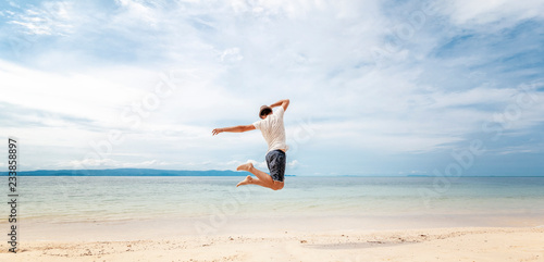 Leinwandbild Motiv Young man in hat  jumping on the beach in front of ocean with feeling happy and freedom