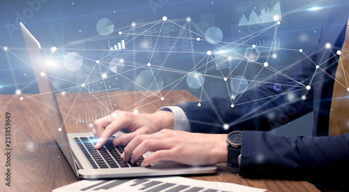 Businessman typing on laptop with linked reports charts grapghs around