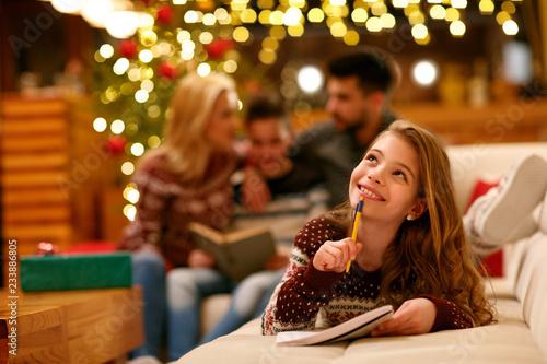 Leinwandbild Motiv smiling girl lying and writes letter to Santa Claus for Christmas.