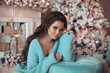 Leinwandbild Motiv Christmas Portrait of Beautiful brunette girl wears in turquoise knitted woolen sweater over gift boxes and xmas decoration interior. Attractive pretty woman with long wavy hair style. Cardigan cloth.