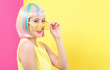 Young woman in a colorful wig with shutter shades sunglasses on a split yellow and pink background