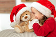 Leinwandbild Motiv Cute young girl wearing santa hat whispering a secret to her teddy bear christmas present toy. Cheeky kid sharing secrets with teddy bear.