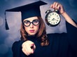 Redhead student girl in cap and gown holding a metal classic alarm clock on green background with bokeh