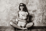 Sad grunge girl near wall with teddy bear. Image in black and white color style © Masson