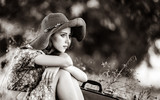 Young girl in hat and dress with suitcase sitting at autumn season grass. Image in black and white color style - 233943458