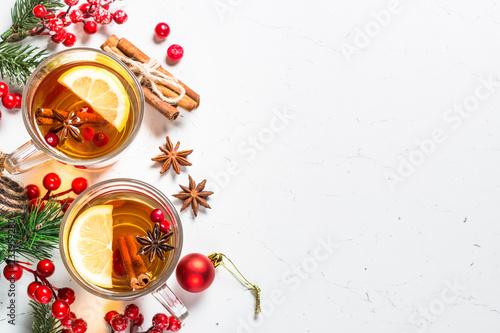 Leinwandbild Motiv Winter hot tea with fruit, berries and spices on white table.