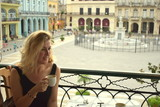 woman sitting on terrace and drinking Cuban coffee