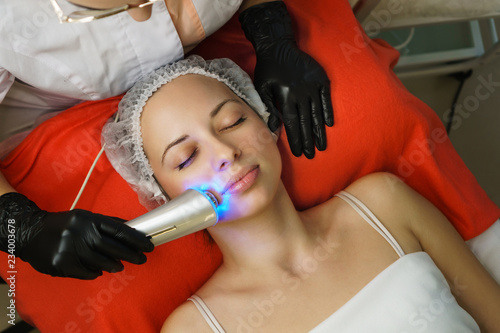 Leinwandbild Motiv Hardware cosmetology. Beautician makes chromotherapy ultrasound cleaning the client's face. Skin pore cleansing. Anti-aging treatments. Spa. Non-invasive therapy