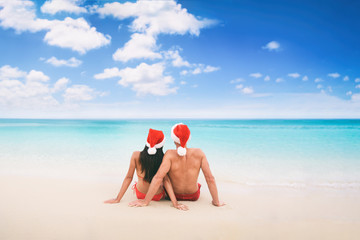 Christmas beach vacation holidays santa hat couple relaxing from behind sitting on white sand blue sky background for text advert for holiday season.