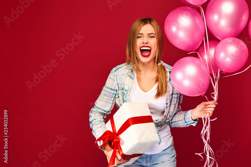 excited young girl in hipster clothes woman model celebrating and holding box with gift present