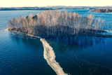 Uninhabited island with birches in the middle of a freezing lake, aerial view - 234040028