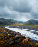 Typical Iceland landscape with river and mountains. Dramatic sky and red stones on a foreground - 234042497