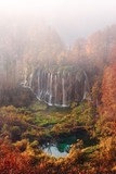 Aerial view on amazing foggy waterfall in Plitvice lakes. Orange autumn forest on background. Plitvice National Park, Croatia. Landscape photography - 234043865