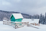 Fantastic winter landscape with green wooden chapel and house in snowy mountains. Christmas holiday concept. Carpathians mountain, Ukraine, Europe - 234045041