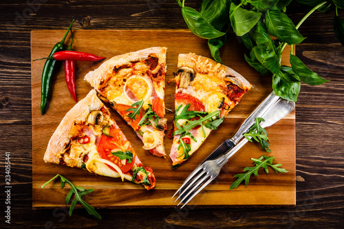 Pizza with pepper,ham and champignon on cutting board on wooden table