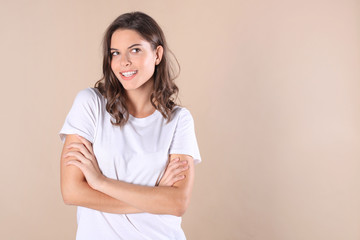 Cheerful brunette woman dressed in basic clothing looking at camera, isolated on beige background. © ty