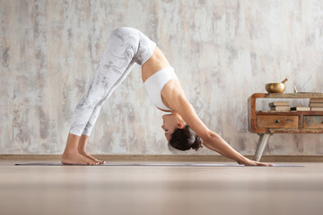Young attractive woman stretching body in yoga asana at home against concrete wall. Girl standing in Downward facing dog exercise, adho mukha svanasana pose, wearing white sportswear. Freedom concept.