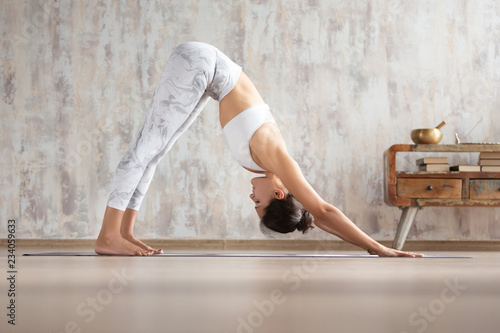 Fototapeta Young attractive woman stretching body in yoga asana at home against concrete wall. Girl standing in Downward facing dog exercise, adho mukha svanasana pose, wearing white sportswear. Freedom concept.